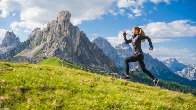 vidéos et rushes de femme d'ajustement s'exécutant en montée sur une prairie herbeuse avec des montagnes en arrière-plan sur une journée ensoleillée - qui monte