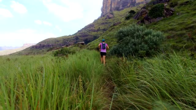 fit woman runs along an extreme mountain trail - cross country running stock videos & royalty-free footage