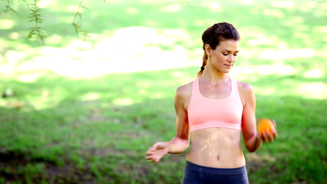 Fit woman throwing an orange in the park