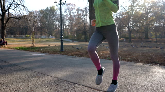 fit woman warming up before running in the park - fitness tracker stock videos and b-roll footage