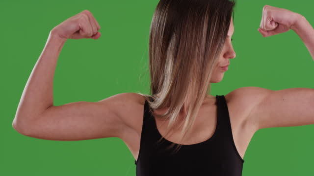 Fit young millennial woman flexing biceps and kissing her muscles on greenscreen