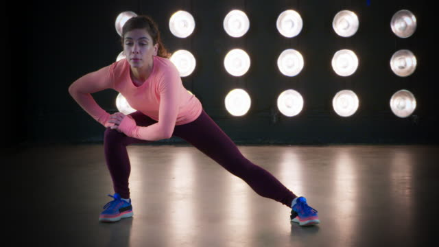 fit young woman alternating side leg stretches during workout 4k - vesper stock stock videos & royalty-free footage