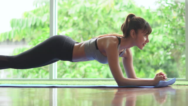 fit young woman doing plank exercise at home - abdominal muscle stock videos & royalty-free footage