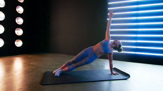 fit young woman doing stretches on floor mat during workout 4k - vesper stock stock videos & royalty-free footage