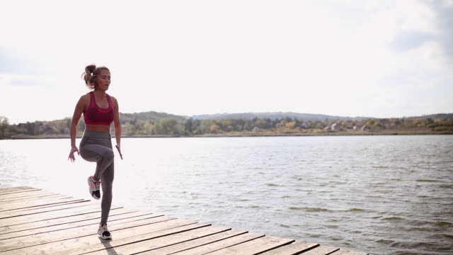 Fit young woman jumping rope at the lake