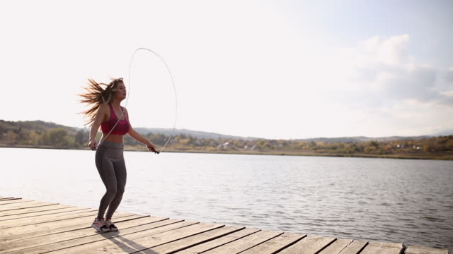 fit young woman jumping the rope at the lake - washboard stock videos and b-roll footage