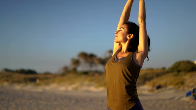 Fit young woman stretching arms at beach