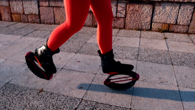 Fitnes woman running in kangoo jump shoes