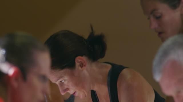 Fitness bootcamp featuring men and women working out and sweating during a grueling exercising class on stationary bicycles.