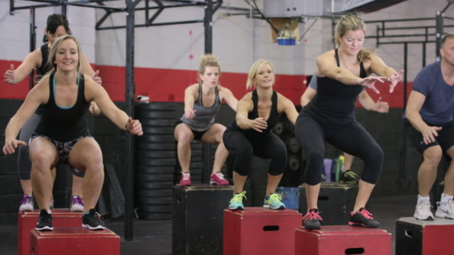 fitness class doing box jumps - fatcamera stock videos and b-roll footage