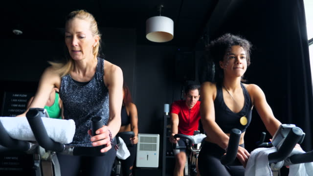 ms fitness class riding stationary bikes during class in cycling studio - fitnesskurs stock-videos und b-roll-filmmaterial