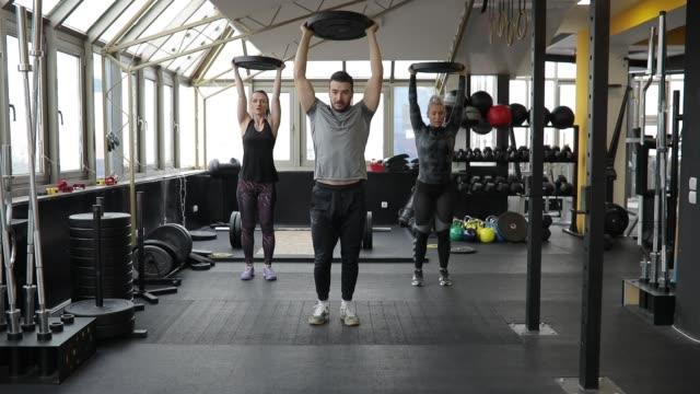 fitness coach e donne in allenamento di sollevamento pesi in palestra - cura della persona video stock e b–roll