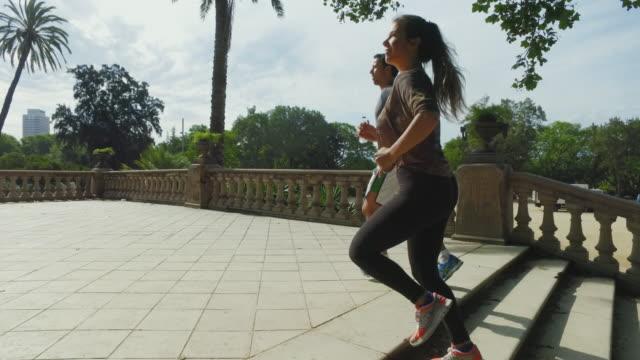 フィットネスカップルジョギングを一緒に公園 - アスレチック点の映像素材/bロール