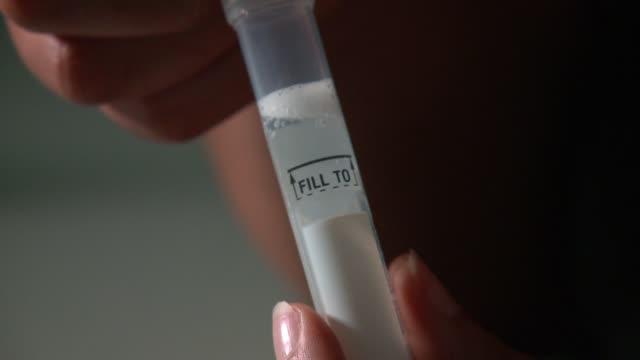 vídeos de stock e filmes b-roll de wgn fitness genes's dna testing kit tube filled with spit on may 10 2017 - banco de areia