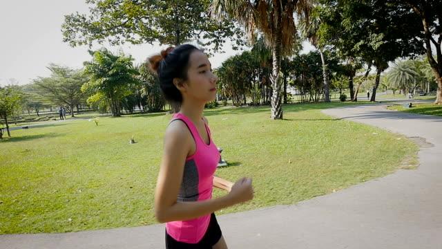 vidéos et rushes de fille de remise en forme en cours d'exécution au parc en plein air, asian coureur féminin en cours d'exécution sur la route à l'extérieur - joggeuse