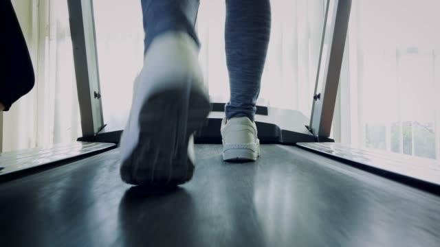 vidéos et rushes de fille de fitness marche sur tapis roulant, fermeture vers le haut de femme avec des jambes musclés dans la salle de gym - membres du corps humain