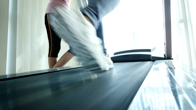 Fitness girl walking on treadmill, Close up of woman with muscular legs in gym