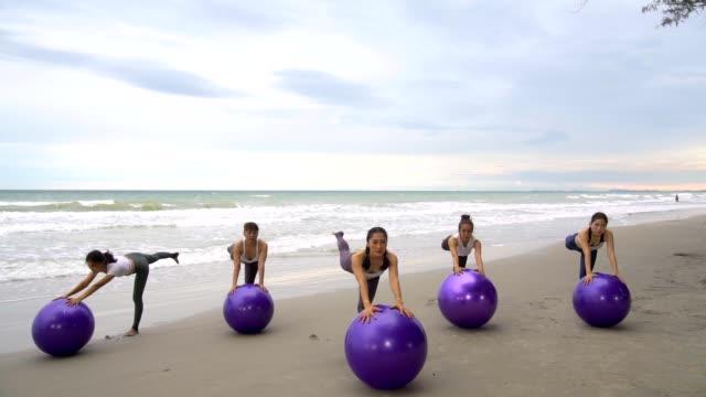 vídeos y material grabado en eventos de stock de grupo de fitness haciendo yoga en la playa. - pilates
