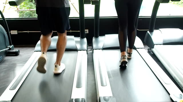 fitness health care concept. man and woman running in machine treadmill at fitness gym - man and machine stock videos & royalty-free footage
