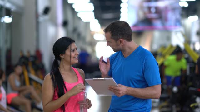 fitness-trainer und frau im gespräch über den trainingsplan - fitnesseinrichtung stock-videos und b-roll-filmmaterial