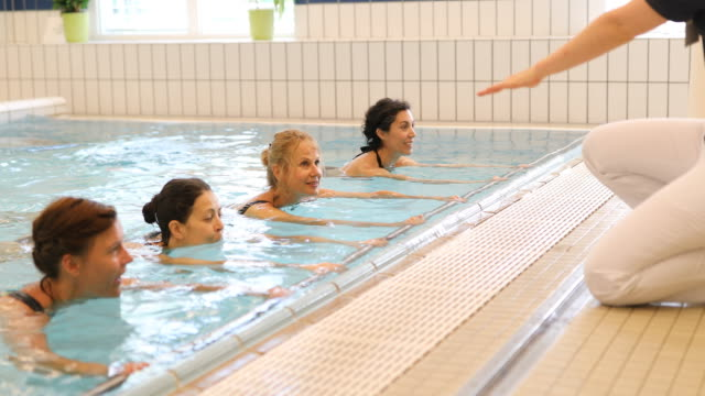fitness instructor assisting women at aqua gym - instructor stock videos & royalty-free footage