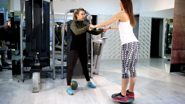 fitness instructor assisting young woman with waist exercise - disk stock videos and b-roll footage