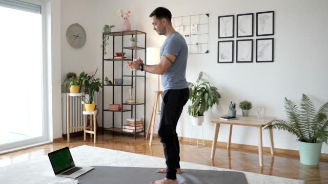 vídeos y material grabado en eventos de stock de instructor de fitness haciendo couches y sentadillas en casa en estera de ejercicio, frente a la computadora portátil con transmisión en vivo - sports training