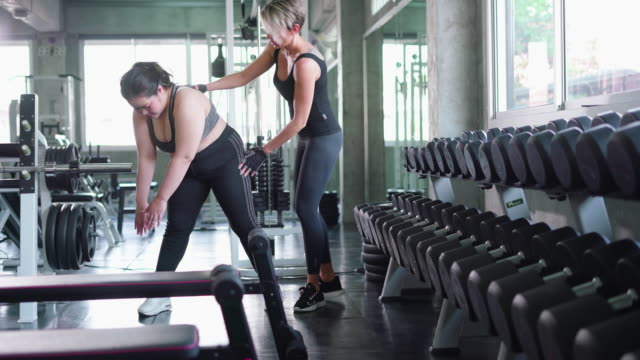 fitness instructor helps young woman with exercise - fitness instructor stock videos & royalty-free footage