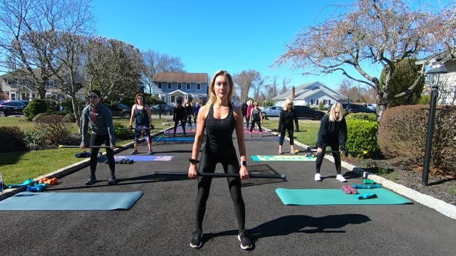 fitness instructor jamie benedik conducts a fitness class in the driveway of her home on march 26, 2020 in west islip, new york. she is an instructor... - home economics点の映像素材/bロール