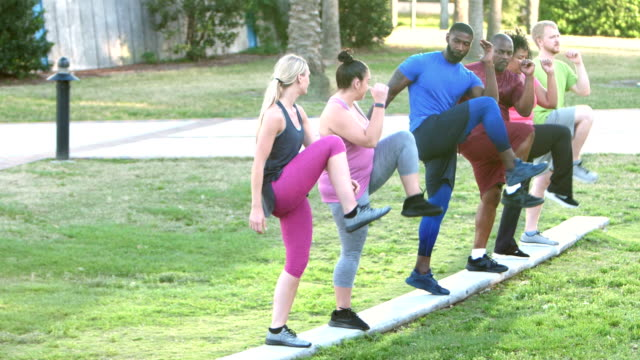 fitness instructor leading multi-ethnic exercise class - fitness instructor stock videos & royalty-free footage