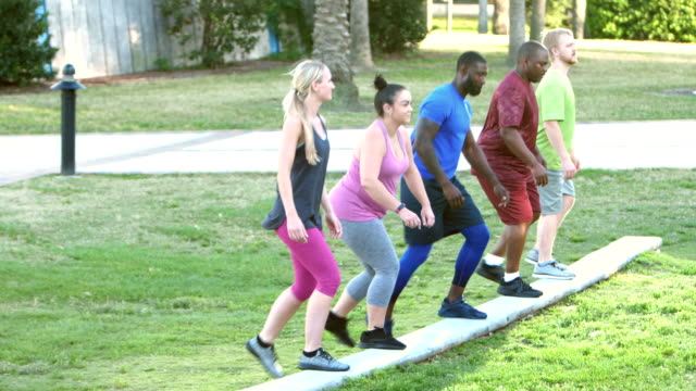 fitness instructor leading multi-ethnic exercise class - exercise class stock videos & royalty-free footage