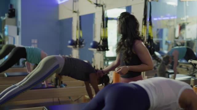 fitness instructor teaching woman doing balancing exercise on pilates reformer exercise machine / lehi, utah, united states - lehi stock videos & royalty-free footage