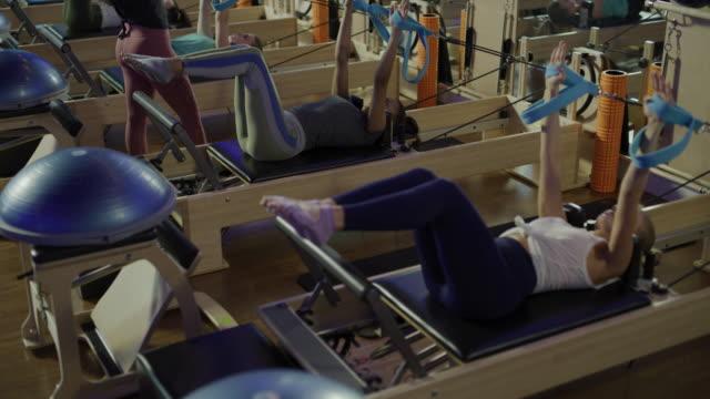 fitness instructor teaching women doing leg lifts laying on pilates reformer exercise machines / lehi, utah, united states - lehi stock videos & royalty-free footage