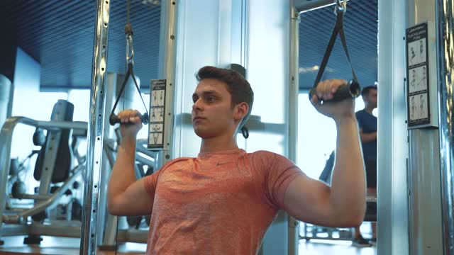 fitness instructor working out, doing cable crossover in health club - arm curl stock videos & royalty-free footage