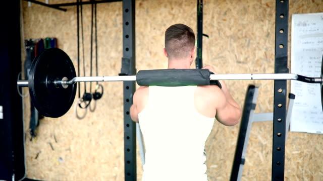 vídeos y material grabado en eventos de stock de atleta masculino de gimnasio levantando pesas en el gimnasio - entrenamiento sin material