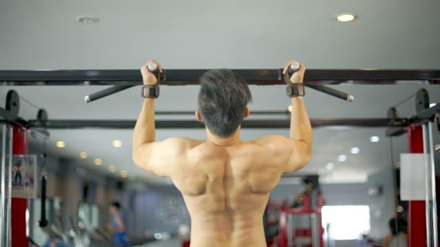 vídeos y material grabado en eventos de stock de fitness hombre haciendo pull ups en el gimnasio - forzudo