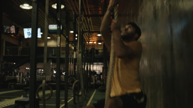 Fitness rope climb exercise in gym workout