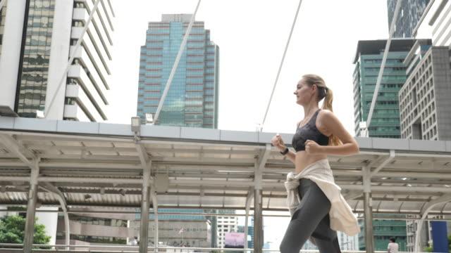 vídeos de stock, filmes e b-roll de corredor de aptidão em execução na cidade - sutiã para esportes