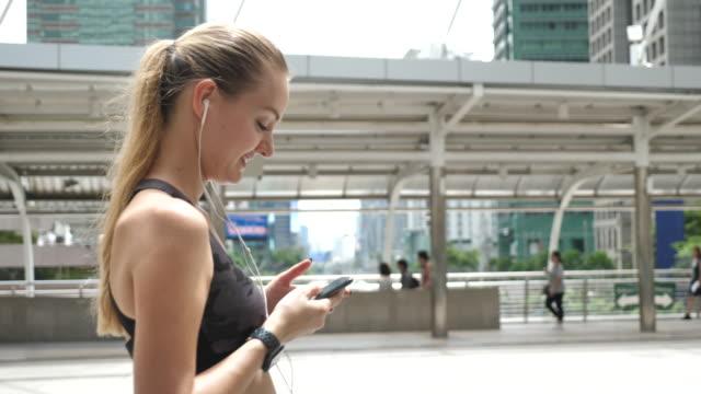 フィットネス ランナー歩行と都市、都市生活、音楽のモバイルのスマート フォンで見る - 女点の映像素材/bロール