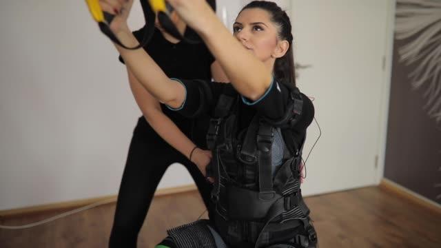 vídeos y material grabado en eventos de stock de trainer fitness ayuda a una mujer en entrenamiento - fisioterapia deportiva