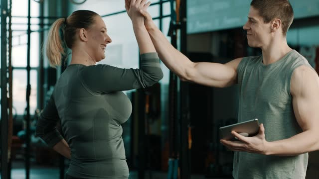 fitness trainer in gym talking to client about results and celebrating with high five - fitness instructor stock videos & royalty-free footage