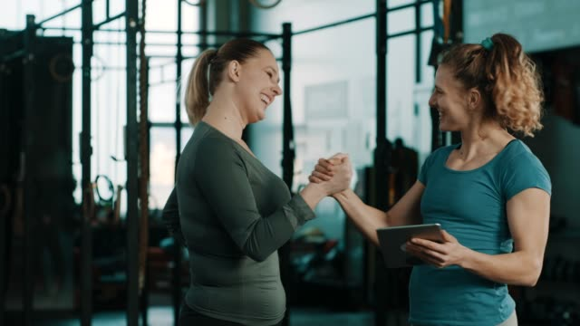 fitness trainer in gym talking to client about results and celebrating with high five - dieting stock videos & royalty-free footage