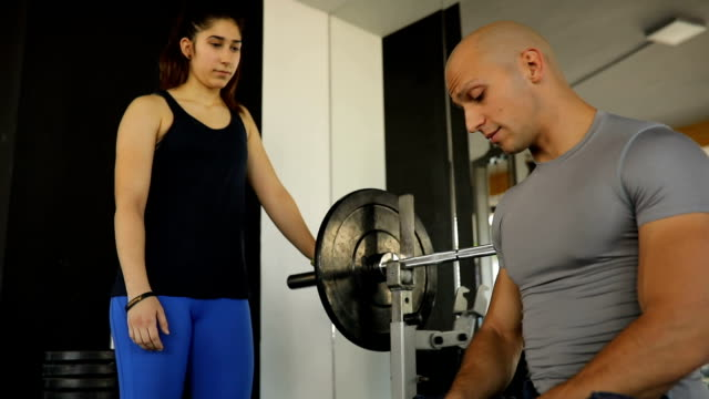 Fitness trainer showing bench press training to a girl