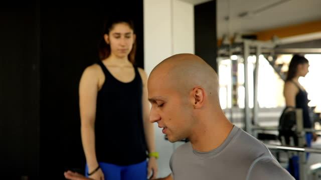 Fitness-Trainer mit Bankdrücken Training zu einer Frau
