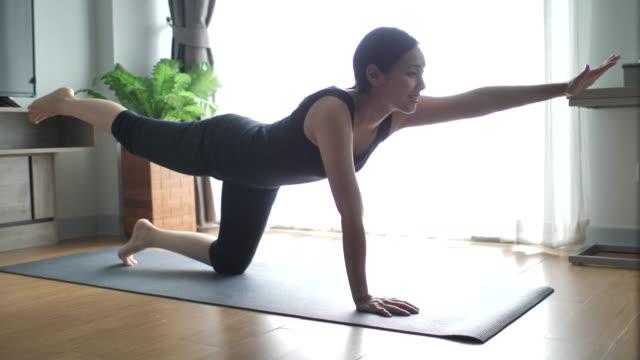 fitness-frau tut bewegung im wohnzimmer zu hause - trainingsraum wohnraum stock-videos und b-roll-filmmaterial