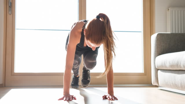 fitness woman doing mountain climber exercise at home - postura video stock e b–roll