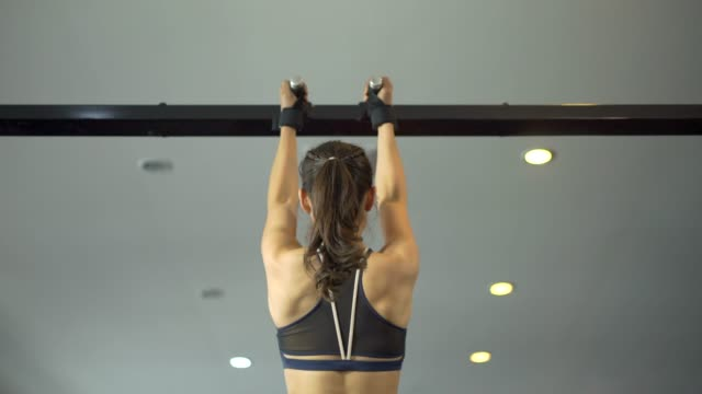 fitness woman doing pull ups at the gym - chin ups stock videos and b-roll footage