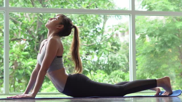 vídeos de stock, filmes e b-roll de mulher da aptidão que faz a ioga em casa - pilates