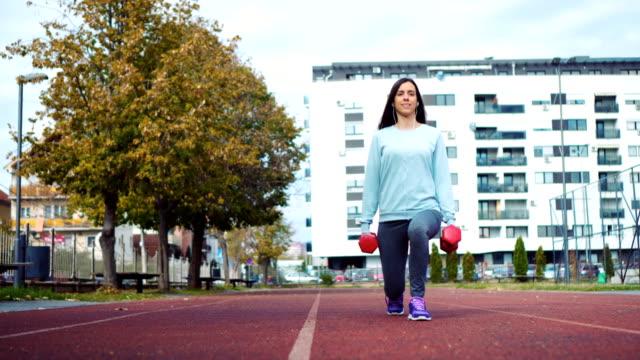 vidéos et rushes de femme de remise en forme entraînement avec poids - fesses