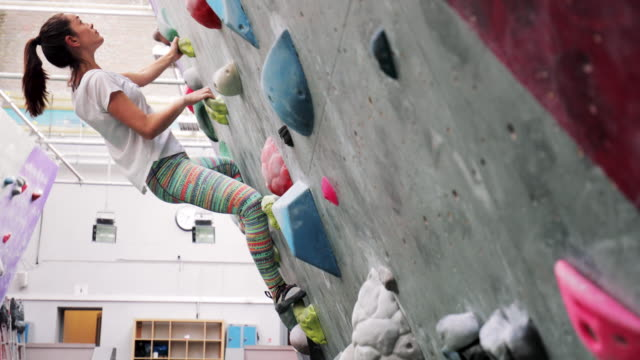 fitness woman on climbing wall - prendersi cura del corpo video stock e b–roll